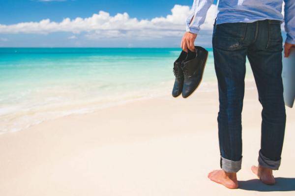 un uomo in spiaggia con abito tiene scarpe e computer in mano e osserva il mare